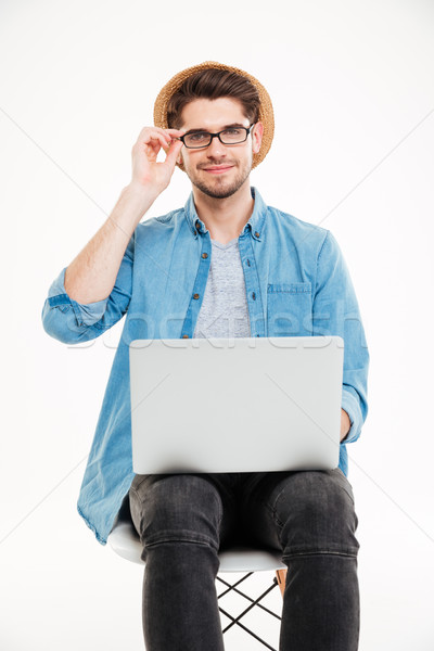 Smiling young man in glasses and hat using laptop Stock photo © deandrobot