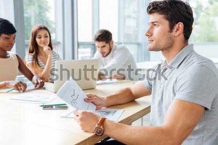 Három koncentrált fiatal üzletemberek dolgozik iratok Stock fotó © deandrobot