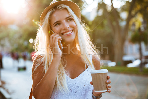 Girl holding take away coffee cup and talking on smartphone Stock photo © deandrobot