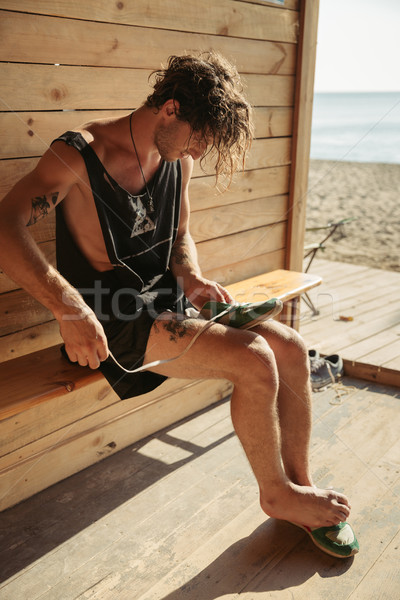 Man ties shoelaces at the beach shack Stock photo © deandrobot