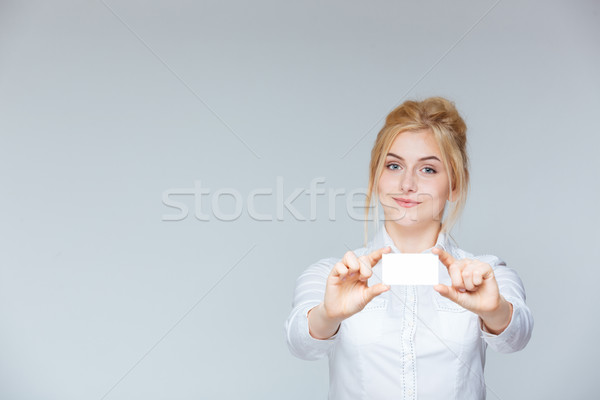 Happy attractive young businesswoman showing blank business card Stock photo © deandrobot