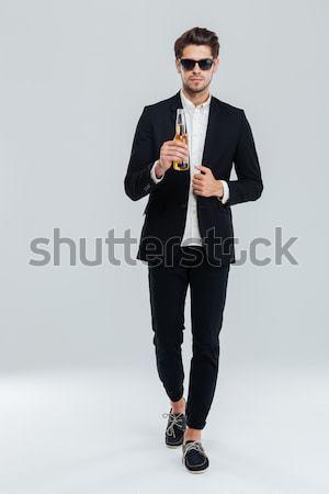 Handsome serious businessman in black sunglasses holding beer bottle Stock photo © deandrobot