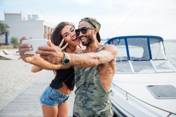 Portrait of a happy couple making selfie photo on smartphone Stock photo © deandrobot
