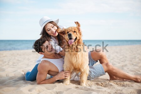 Beautiful loving couple playing with their dog at the seaside Stock photo © deandrobot