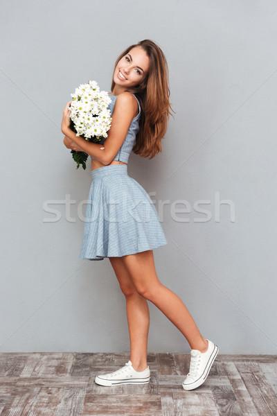 Boldog aranyos fiatal nő áll tart virágcsokor Stock fotó © deandrobot