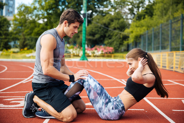 Young beautiful couple doing exercises at the stadium Stock photo © deandrobot