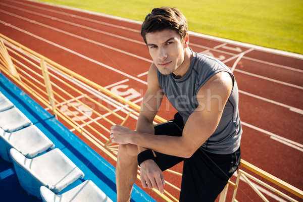 Young sportsman leaning on the railing and resting after workout Stock photo © deandrobot