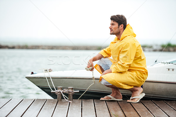 Sailor in yellow cloak holding rope at the pier Stock photo © deandrobot