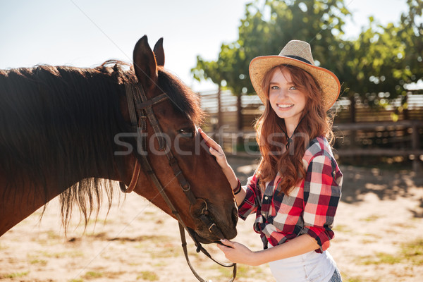Pretty lovely cowgirl taking care of her horse on ranch Stock photo © deandrobot