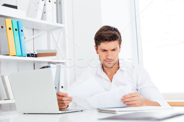 Handsome young businessman analyzing documents and laptop in office Stock photo © deandrobot