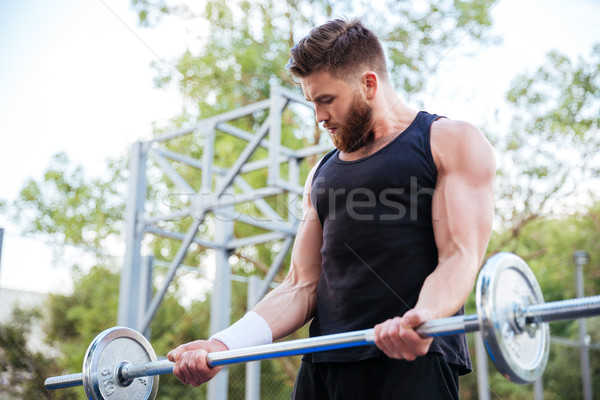 Serious young man athlete exercising and lifting barbell Stock photo © deandrobot