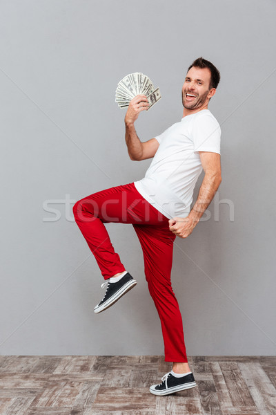 Cheerful excited young man holding dollars and celebrating success Stock photo © deandrobot