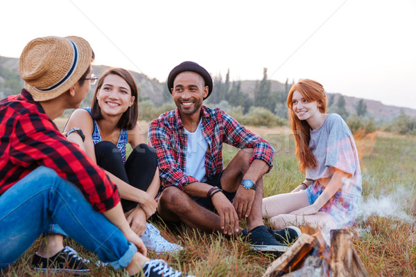 Happy young people sitting near campfire together Stock photo © deandrobot