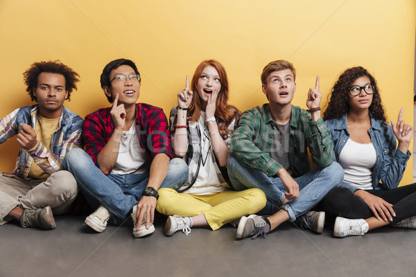 Multiethnic group of smiling young people sitting and pointing up Stock photo © deandrobot