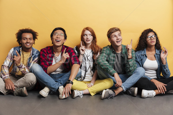 Multiethnic group of happy people pointing up and having idea Stock photo © deandrobot