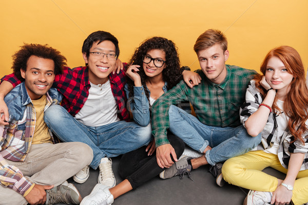Multiethnic group of happy young people sitting and hugging together Stock photo © deandrobot
