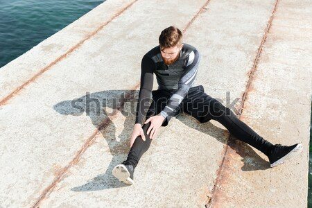 Guy warming up near the sea Stock photo © deandrobot