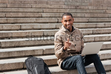 Young african cheerful man sitting on staircase and using laptop Stock photo © deandrobot