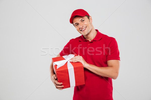 Smiling delivery man with christmas gift Stock photo © deandrobot