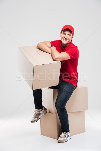 Boldog futár ül dobozok néz kamera Stock fotó © deandrobot