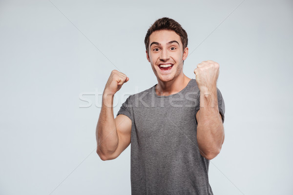 Man celebrating success with two fists in the air Stock photo © deandrobot