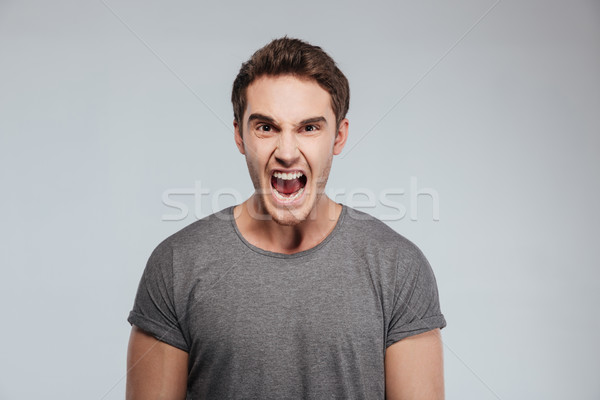 Portrait of a angry man screaming and looking at camera Stock photo © deandrobot
