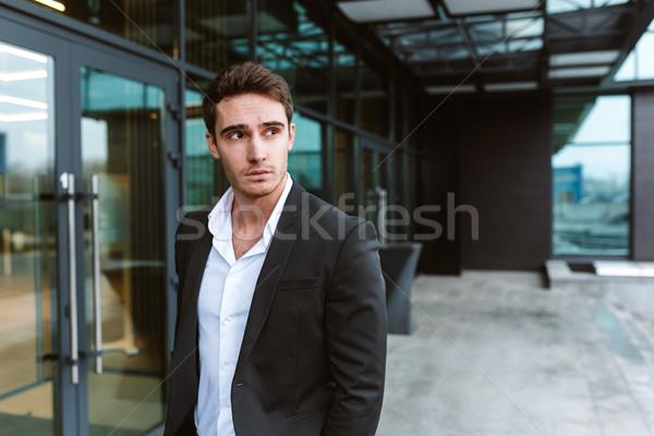 Serious business man near the office Stock photo © deandrobot