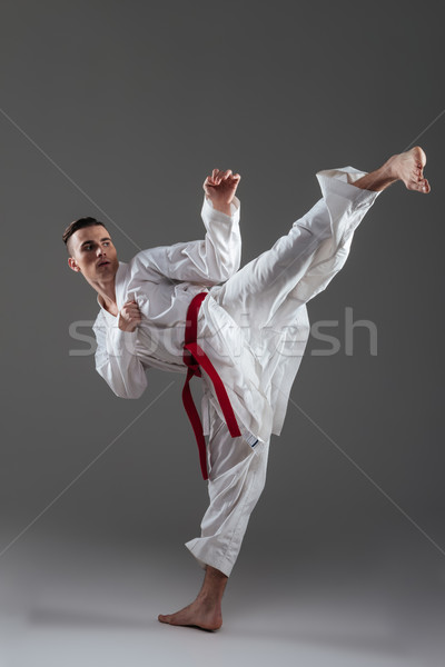 Young sportsman dressed in kimono practice in karate Stock photo © deandrobot