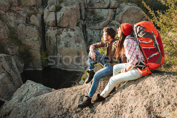Adventure couple sitting on a rock Stock photo © deandrobot
