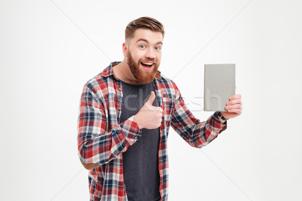 Man in plaid shirt holding book and showing thumb up Stock photo © deandrobot