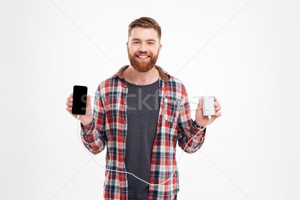 Attractive smiling man charging his mobile phone Stock photo © deandrobot