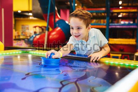 Cheerful little boy playing air hockey game at indoor playground Stock photo © deandrobot