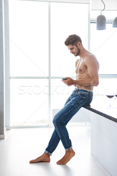 Shirtless man standing and using cell phone at home Stock photo © deandrobot