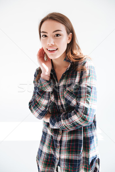Cheerful lovely yung woman in plaid shirt standing and smiling Stock photo © deandrobot
