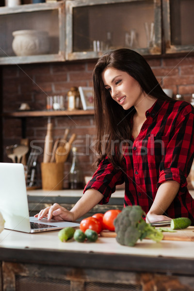 Vertical image of woman standing in kitchen with laptop Stock photo © deandrobot