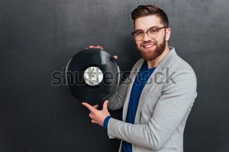 Happy young man in glasses holding and pointing on turntable Stock photo © deandrobot
