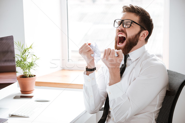 Screaming angry businessman sitting in office Stock photo © deandrobot