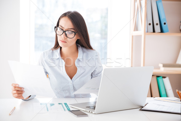 Businesswoman using laptop while looking at documents Stock photo © deandrobot