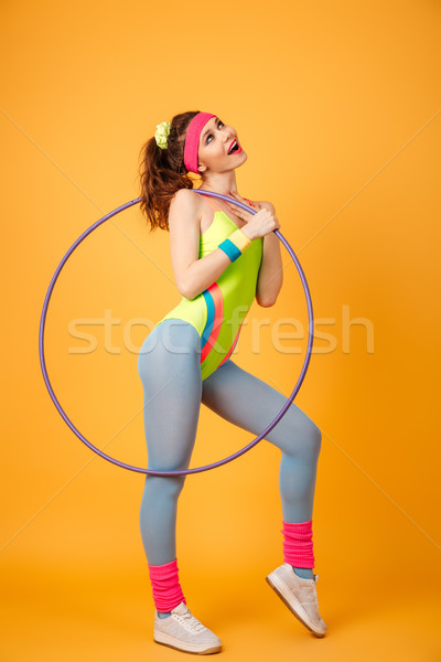Smiling pensive young sportswoman with hula hoop standing and dreaming Stock photo © deandrobot