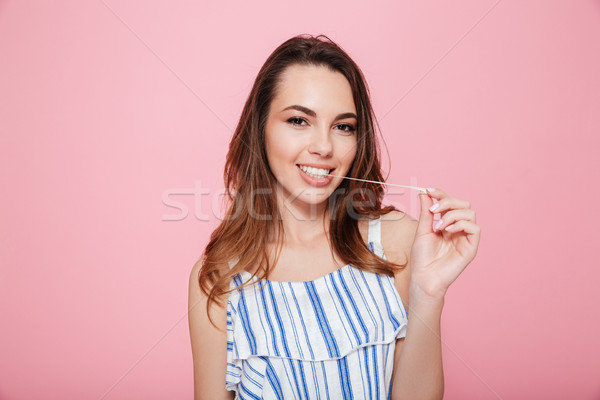 Happy lovely young woman standing and chewing bubble gum Stock photo © deandrobot