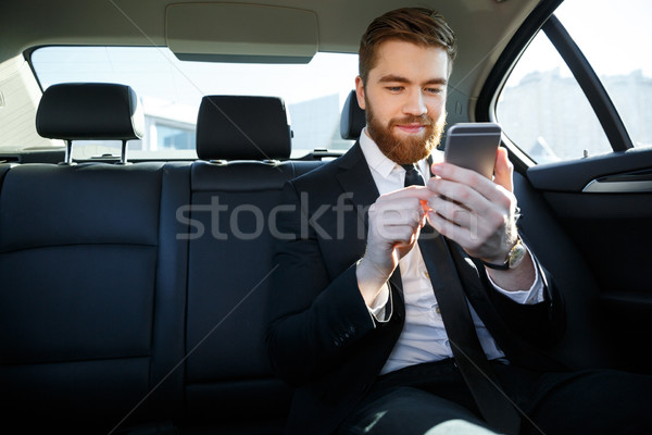 Man in suit looking at mobile phone in his hand Stock photo © deandrobot
