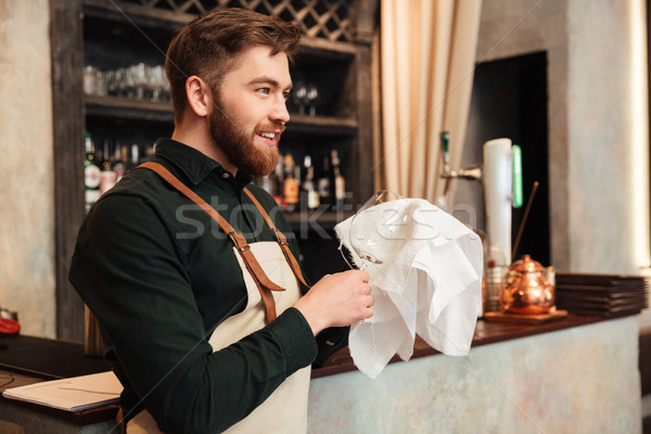 Happy young bearded man bartender standing in cafe. Stock photo © deandrobot