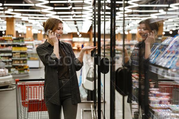 Glimlachend jonge dame permanente supermarkt kiezen Stockfoto © deandrobot