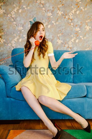 Serious young pin-up lady talking by phone. Stock photo © deandrobot