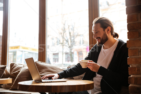 Happy Bearded man using laptop in cafe Stock photo © deandrobot