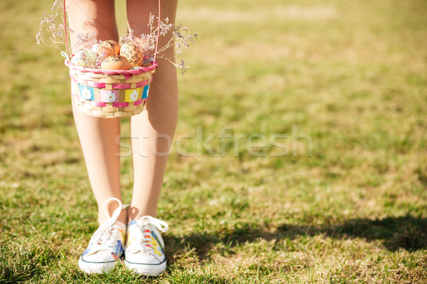 Young girls legs and basket with painted easter eggs outdoors Stock photo © deandrobot