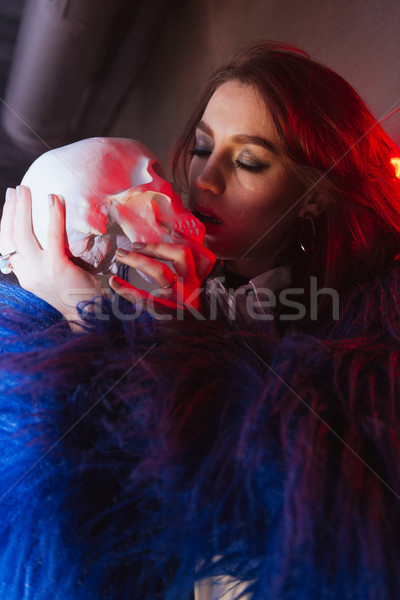 Young lady standing and holding artificial skull. Stock photo © deandrobot