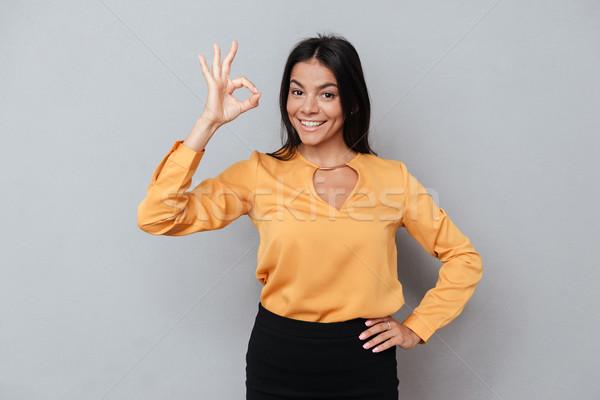Mosolyog üzletasszony mutat oké kézmozdulat néz Stock fotó © deandrobot
