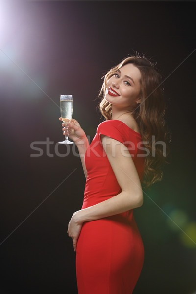 Happy beautiful woman in red dress stading and drinking champagne Stock photo © deandrobot