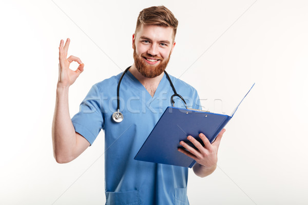 Confident doctor or nurse with clipboard in hand showing okay gesture Stock photo © deandrobot